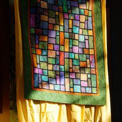 Der Quilt, das Geschenk für Heidi Wäger, hängt über dem Altar.